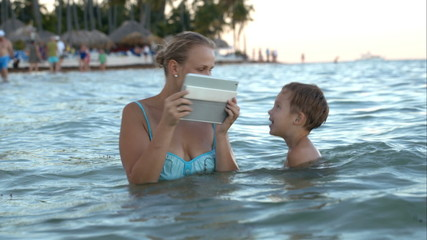 Mother with pad making photo or video of son in water