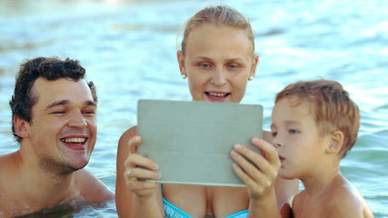 Family of three in sea watching something on pad