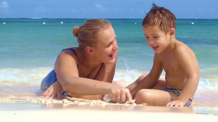 Boy watching mother drawing on sand