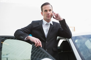 Serious businessman using his phone