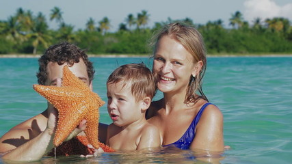 Parents and son in sea water holding starfish