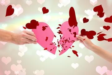 Composite image of hands holding two halves of broken heart