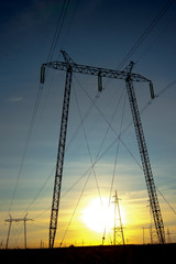 Silhouette of high voltage power transmission lines and pylons a