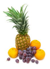 pineapple, dark grapes and tangerines isolated on a white backg