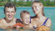 Parents and their little son in sea water holding starfish