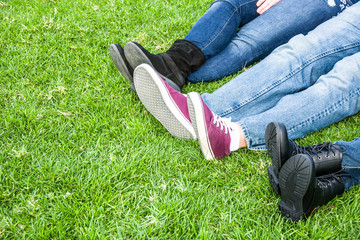 Three people shoes on grass