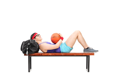 Young man lying on a bench and holding basketball