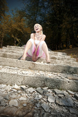 Cute woman sitting on stairs and acting surprised