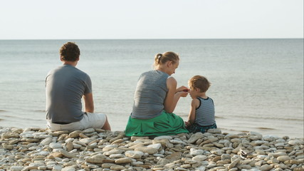 Family of three sitting on pebble beach by the water
