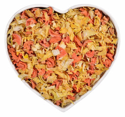 Dried carrots and onions in plate in the form of heart on a whit
