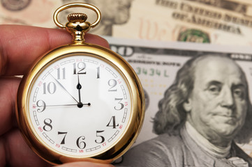 Hand holding watch on dollar banknotes