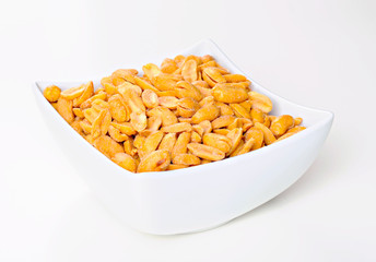 Roasted and salted peanuts on a white bowl, white background