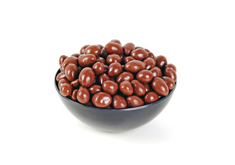 Peanuts covered by milk chocolate, on a black bowl
