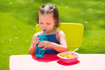 Toddler kid girl drinking eating pasta in garden