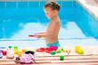 Toddler kid girl playing food toys in swimming pool