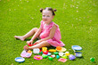 Toddler kid girl playing with food toys sitting in turf