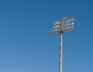 The Stadium spot-light tower over blue sky background.