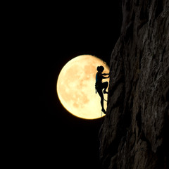 Female rock climber ascends the natural rock at night