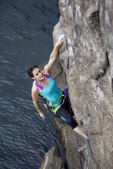 Female rock climber hanging over the sea