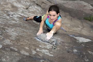 Female extreme climber makes hard move