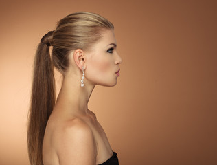 Portrait of fashionable woman with long hair tail in profile