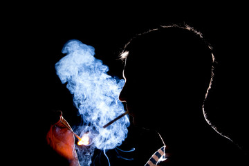Silhouette of man who lights the cigarette in the dark