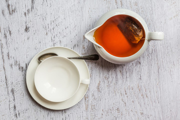 White cup of tea with kettle, top view point