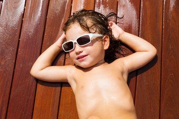 Toddler baby kid in summer sun tanning on wood