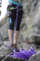 Purple climbing rope and legs of climber