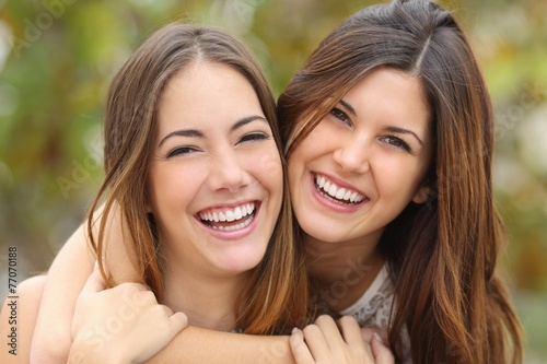 Leinwanddruck Bild Two women friends laughing with a perfect white teeth