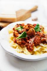 Farfalle pasta with chicken, tomato sauce and mushrooms