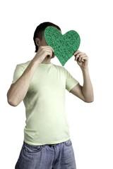 молодой человек закрыл лицо игрушечным зеленым сердцем