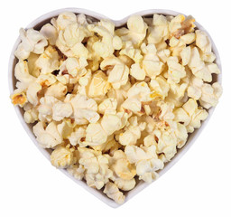 Fresh popcorn in plate in the form of heart on a white