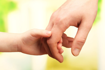 Child and father hands on bright background