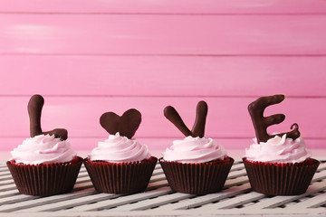 Delicious Valentine Day cupcake on pink wooden background