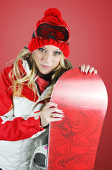 Female snowboarder posing with a snowboard.