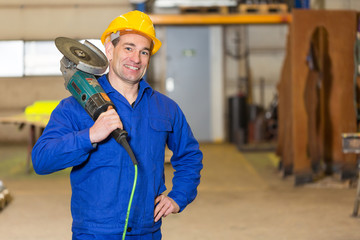 Steel construction worker posing with angle grinder