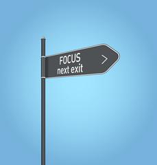 Focus next exit, dark grey road sign