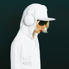 Sensual blonde DJ in sports white clothing listening to Music on