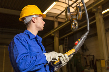 Construction worker operating crane in assembly hall