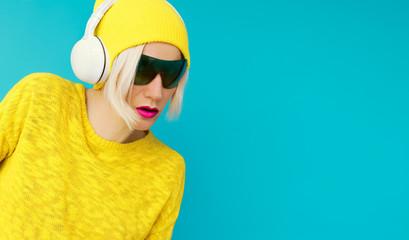 Glamurus blonde DJ in bright clothes listening to Music on blue