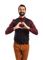Man wearing waistcoat making a heart with his hands
