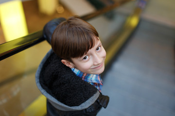Little boy looking back on escalator