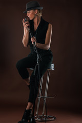 beautiful blond woman with a microphone sitting on bar chair