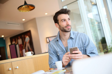 Man in coffee shop sending message with smartphone