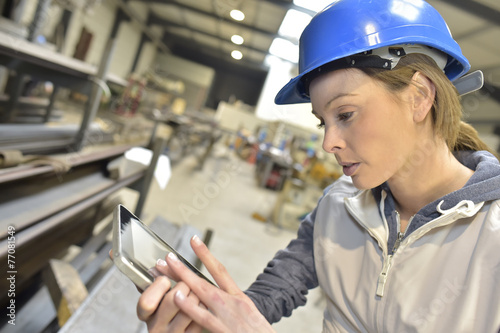 Woman engineer in steel plant checking production - 77081549