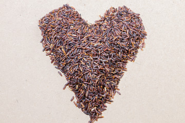 Close-up heart shape brown rice on wooden background