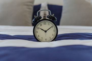 black classic alarm clock on bed