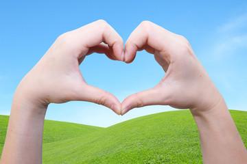 hand in heart shape on the green field