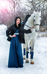 Girl in blue on a White  horse in winter
